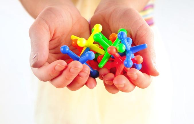 Child holding set of colorful jacks