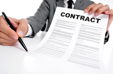 man wearing a suit sitting in a table showing a contract and whe